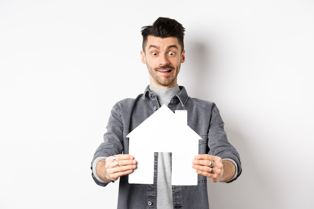 Pojęcie nieruchomości i ubezpieczenia. mężczyzna patrzy z podekscytowaniem na wycinankę domu papieru, kupuje dom, stojąc na białym tle.