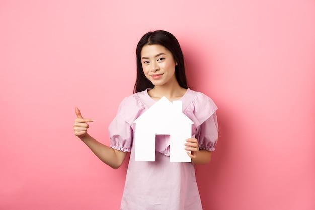 Pojęcie nieruchomości i ubezpieczenia. piękna azjatka, wskazując na wycinankę domu papieru, pokazując logo agencji, stojąc w sukience na różowym tle.