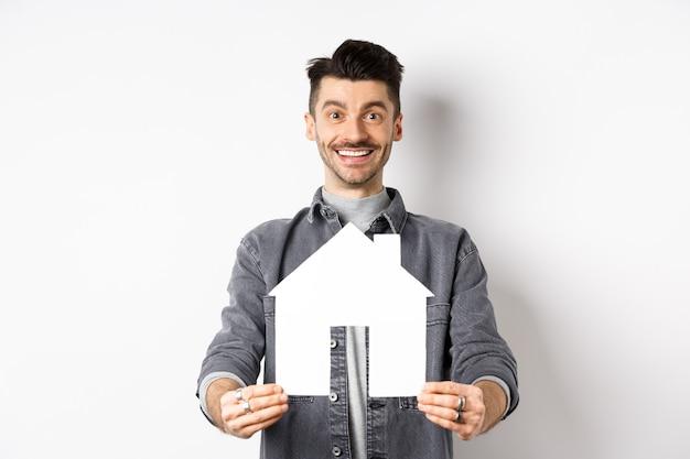 Pojęcie nieruchomości i ubezpieczenia. przystojny młody chłopak pokazując papierowy dom wyłącznik i uśmiechnięty, szukając mieszkania, kupując nieruchomość, stojąc na białym tle.