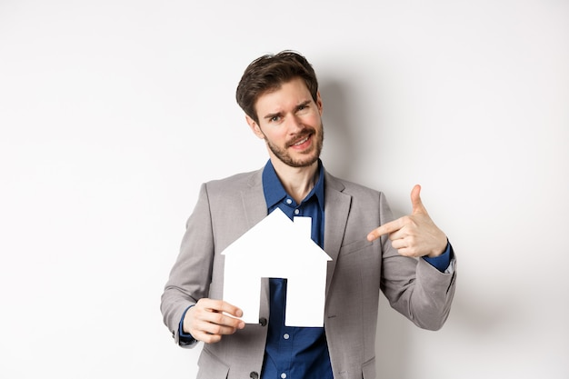 Pojęcie nieruchomości i ubezpieczenia. sprzedawca w szarym garniturze pokazuje wycinek domu z papieru, sprzedaje nieruchomość, uśmiecha się do kamery, białe tło.