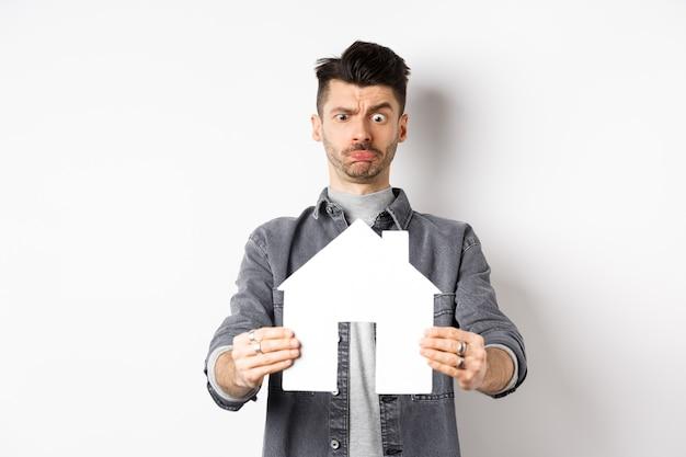 Pojęcie nieruchomości i ubezpieczenia. zdezorientowany facet niepewnie patrzy na wycinankę z papierowego domku, marszczy brwi z zakłopotaniem, stoi na białym tle.