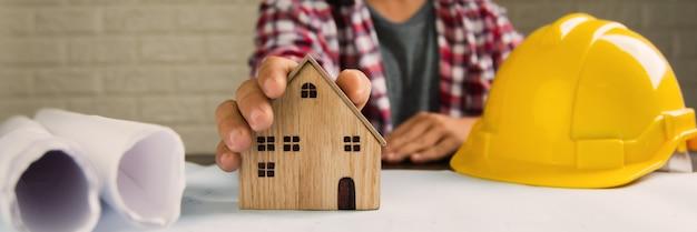Pojęcie nieruchomości, inżynier pokazuje mały dom, architekt i konstruktor
