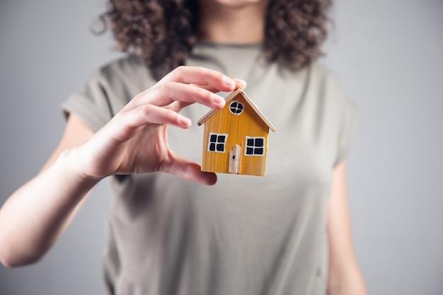 Pojęcie nieruchomości, kobieta trzyma model domu.