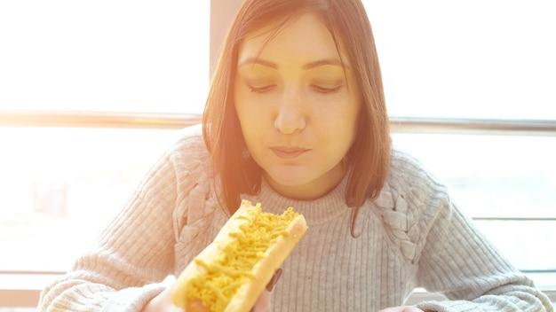 Pojęcie niezdrowej żywności. kobieta je hot doga w kawiarni z apetytem, z bliska