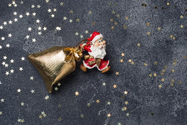 Pojęcie nocy bożonarodzeniowej. mikołaj ciągnie worek prezentów ciemne tło gwiazdy. skopiuj miejsce