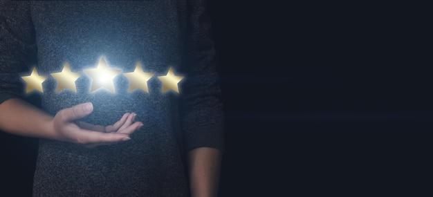 Pojęcie oceny. ręka wskazująca na pięć gwiazdek zwiększa ocenę firmy, zwiększa ocenę
