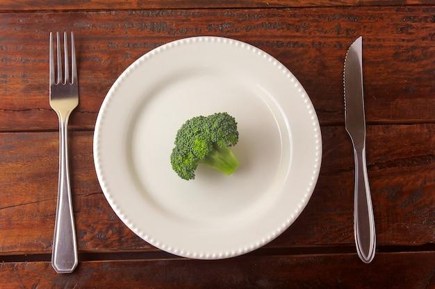 Pojęcie ograniczenia kalorii. ścisła dieta. pokrojony strąk na talerzu z rozwidleniem i nożem na drewnianym stole