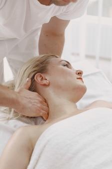 Pojęcie opieki zdrowotnej i kobiecego piękna. masażystki wykonują masaż dziewczyny. kobieta w salonie spa.