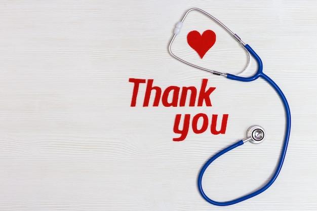 """Pojęcie opieki zdrowotnej i medycznej. stetoskop w kolorze niebieskim, czerwonym sercem i tekst """"dziękuję"""" na białym tle drewnianych z miejsca kopiowania. narodowy dzień pielęgniarek."""