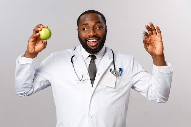 Pojęcie opieki zdrowotnej, medycyny i zdrowego stylu życia. przyjazny afroamerykański lekarz w białym fartuchu, trzymający jabłko i pigułkę, sugeruje, że pacjenci pozostają zdrowi bez leków, jedzą więcej owoców