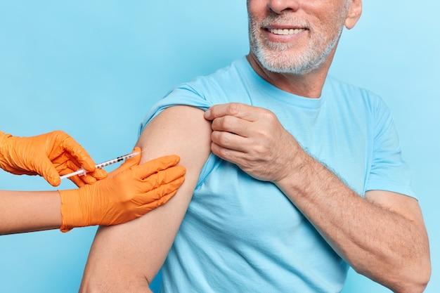 Pojęcie opieki zdrowotnej. nieznany starszy mężczyzna dostaje szczepionkę przeciwko koronawirusowi w ramię nosi luźną koszulkę