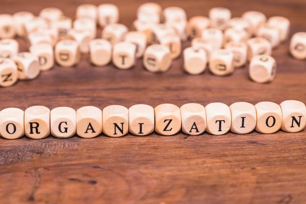 Pojęcie organizacji ułożone z drewnianymi kostkami nad drewnianym biurkiem