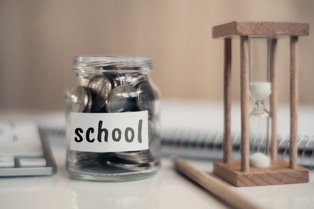 Pojęcie oszczędności dla szkoły - szklany słoik z monetami i napisem.