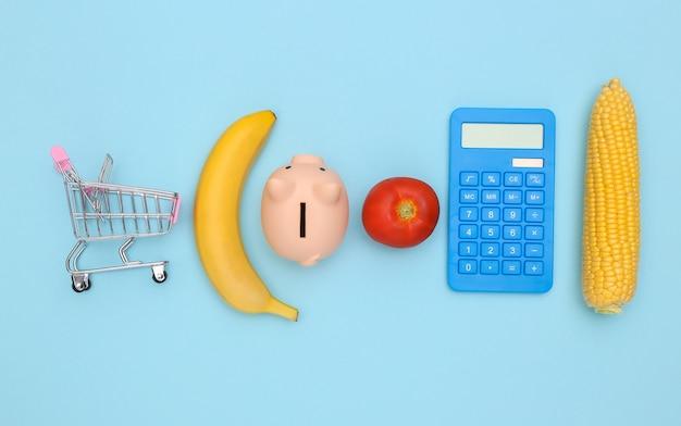 Pojęcie oszczędzania na jedzeniu, zakupy. wózek w supermarkecie, kalkulator, skarbonka, warzywa i owoce na niebieskim tle. minimalizm kompozycji