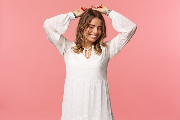 Pojęcie piękna, czułości i mody. atrakcyjna blond kaukaska kobieta z tatuażami w jasnej białej wiosennej sukience, unosi ręce w górę zrelaksowany, uśmiechnięty z zamkniętymi oczami, tańcząca, różowa ściana.