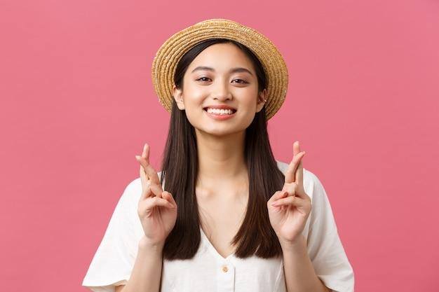 Pojęcie piękna, emocji i wypoczynku i wakacji. zbliżenie pełnej nadziei marzycielskiej azjatyckiej dziewczyny, która marzy na letnią wycieczkę nad morze, ma na sobie słomkowy kapelusz, skrzyżowane palce i uśmiecha się optymistycznie.