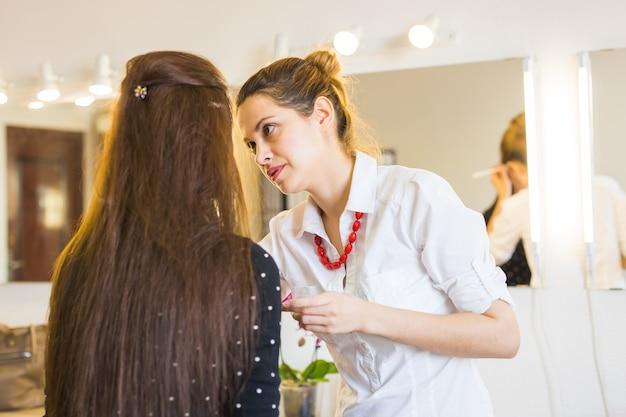 Pojęcie piękna i makijażu - zbliżenie portret pięknej kobiety coraz profesjonalny makijaż z pędzlem.