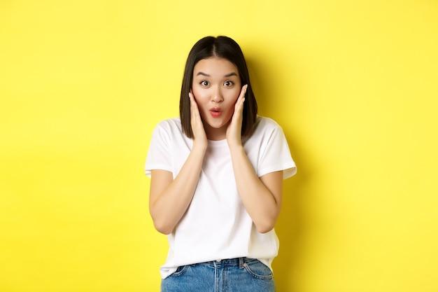 """Pojęcie piękna i mody. azjatka mówiąca """"wow ze zdumieniem"""", sprawdzająca niesamowitą ofertę promocyjną, stojąca na żółtym tle"""