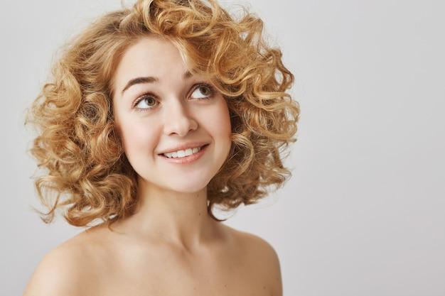 Pojęcie piękna i mody. marzycielska dziewczyna z kręconymi włosami, uśmiechnięta, z nagimi ramionami, patrząca w prawy górny róg