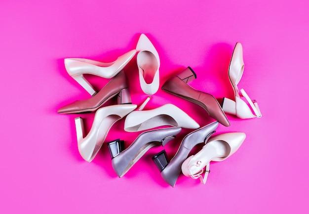 Pojęcie piękna i mody. modne buty damskie na białym tle na różowym tle. widok z góry. buty damskie. stylowe klasyczne damskie skórzane buty. wysoki obcas buty damskie na czerwonym tle.