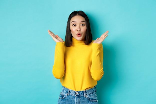 Pojęcie piękna i mody. obraz podekscytowanej i zaskoczonej japonki mówiącej wow ze zdumienia, unoszącej ręce w pobliże twarzy, stojącej na tle błękitu.