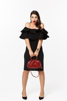 Pojęcie piękna i mody. pełna długość, choć głupia, dąsająca się i wyglądająca na zaskoczoną, trzymająca torebkę, ubrana na obcasach i czarną sukienkę, białe tło.