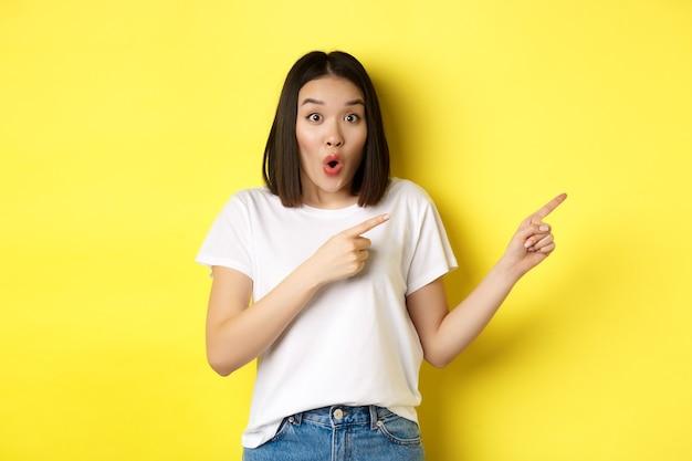 Pojęcie piękna i mody. piękna azjatycka kobieta w białej koszulce wskazując palcami w prawo, demonstruje logo stojące na żółtym tle.