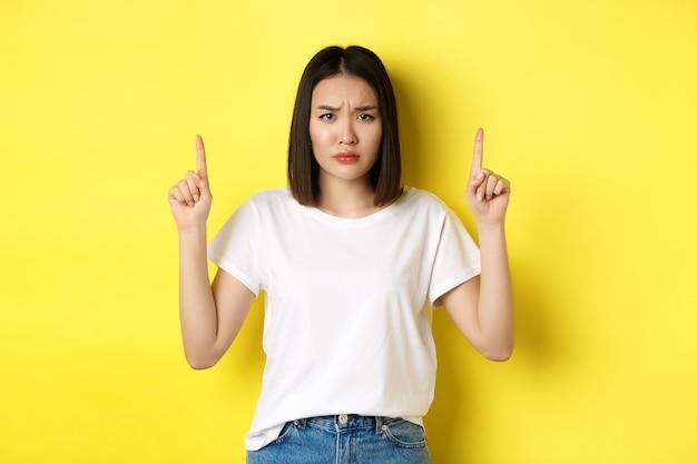 Pojęcie piękna i mody. piękne azjatki kobieta w białej koszulce, wskazując palcami w górę, stojąc na żółtym tle.