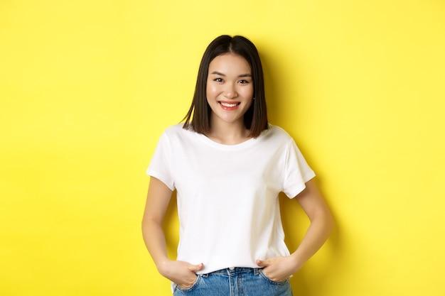 Pojęcie piękna i mody. stylowa azjatka w białej koszulce, uśmiechnięta szczęśliwa i stojąca na żółtym tle.