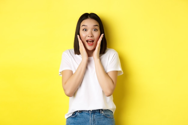 """Pojęcie piękna i mody. zaskoczona azjatka patrząca zdumiona w kamerę, mówiąca """"wow"""", sprawdzająca reklamę, stojąca nad żółtym tłem."""