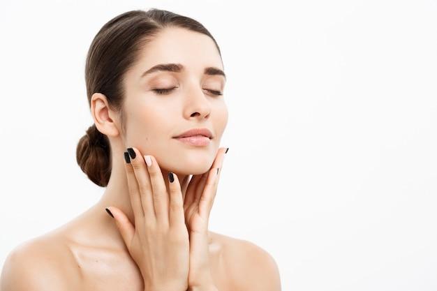 Pojęcie piękna i pielęgnacji skóry - bliska piękna młoda kobieta dotyka jej skóry na białej ścianie.