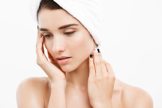 Pojęcie piękna i pielęgnacji skóry - bliska piękna młoda kobieta dotyka jej skóry.