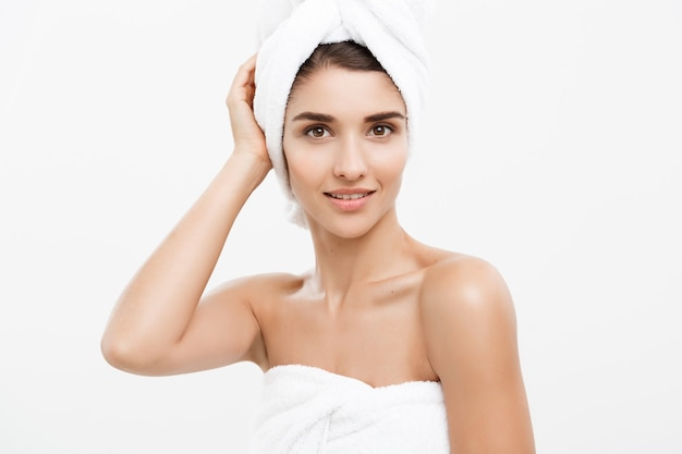 Pojęcie piękna i pielęgnacji skóry - piękna młoda kobieta kaukaski z ręcznikiem na głowie, obejmujące jej piersi, na białym tle.