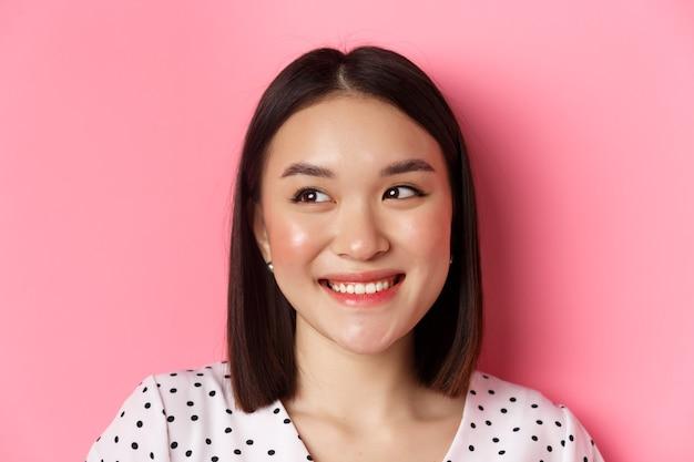 Pojęcie piękna i stylu życia. headshot ładnej azjatyckiej kobiety marzycielskiej patrzącej w lewo na miejsce, uśmiechniętej szczęśliwej, stojącej na różowym tle