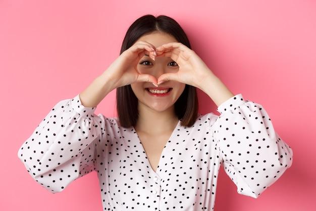 Pojęcie piękna i stylu życia. zbliżenie uroczej azjatyckiej kobiety pokazującej znak serca, uśmiechniętej i czującej się romantycznie w walentynki, stojącej na różowym tle.