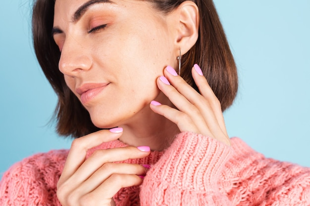 Pojęcie piękna, ładna kobieta z manicure jasny różowy kolor paznokci na ścianie