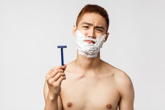 Pojęcie piękna, ludzi i higieny. niechętny i niezadowolony azjatycki mężczyzna nie chce się golić, wygląda na rozczarowaną kamerę wykrzywiającą się, pokazując starą brzytwę, nałóż krem na szczękę, biała ściana