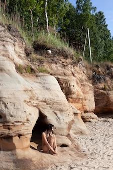 Pojęcie piękna, młodości i zdrowego stylu życia. czarne włosy naga kobieta na piaszczystej plaży w pobliżu jaskiń. naga kobieta pokryta piaskiem obok morskich jaskiń