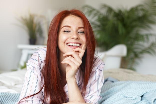 Pojęcie piękna, młodości, radości i szczęścia. urocza śliczna młoda rudowłosa piegowata kobieta ubrana w pasiastą bieliznę nocną, uśmiechnięta radośnie, ciesząca się radosną chwilą, spędzając wolny czas w domu