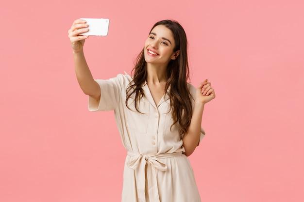 Pojęcie piękna, mody i kobiet. nęcąca młoda kobieca kobieta robi selfie w nowej sukience, publikuje nowe zdjęcie online, uśmiecha się czuła i urocza, stojąc różową ścianę