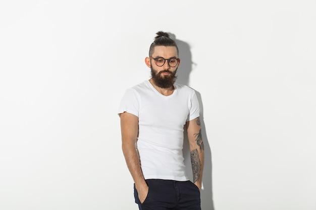 Pojęcie piękna, mody i ludzi - fajny mężczyzna z brodą, pozowanie na białym