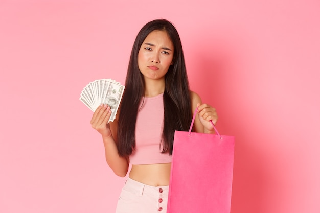 Pojęcie piękna, mody i stylu życia. portret rozczarowanej, dąsającej się azjatki z pieniędzmi i torbą na zakupy wyglądającej na niezadowoloną, próbującej rozweselić kupowaniem nowych ubrań, różowa ściana.