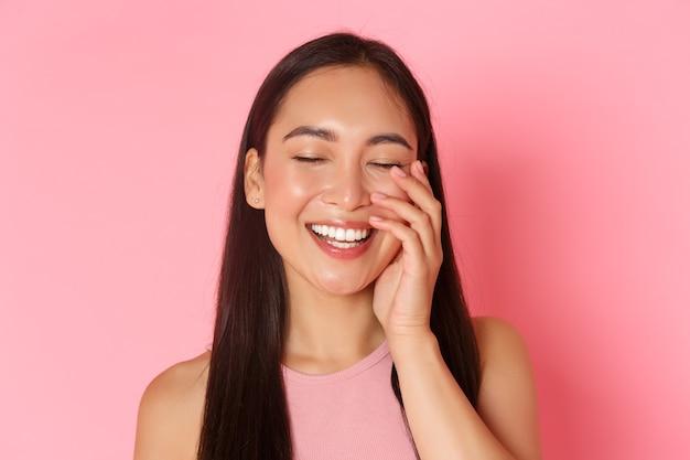 Pojęcie piękna, mody i stylu życia. zbliżenie beztroskiej pięknej azjatki dotykającej twarzy i śmiejącej się radośnie z zamkniętymi oczami, stojącej nad różową ścianą radosną promocją produktu do pielęgnacji skóry.
