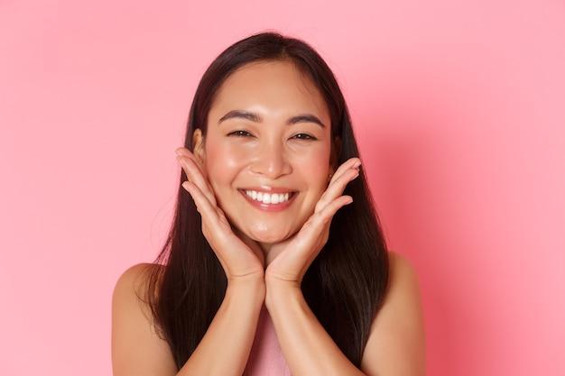 Pojęcie piękna, mody i stylu życia. zbliżenie pięknej azjatyckiej dziewczyny dotykającej jej twarzy i uśmiechającej się głupio, rumieniącej się, czującej się odświeżonej, nakładającej produkt do pielęgnacji skóry lub makijaż, różowa ściana