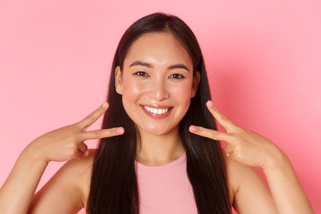 Pojęcie piękna, mody i stylu życia. zbliżenie pięknej azjatyckiej dziewczyny glamour z białym idealnym uśmiechem, czystą twarzą, pokazującą gest pokoju kawaii i wyglądającą szczęśliwą, różową ścianą.