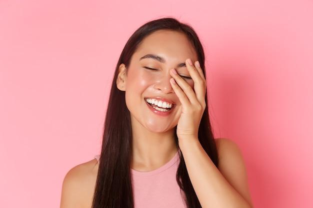 Pojęcie piękna, mody i stylu życia. zbliżenie pięknej azjatyckiej młodej dziewczyny bez trądziku i wyprysków, biały uśmiech, dotykająca twarz i wyglądająca na szczęśliwą, stojąca nad różową ścianą.