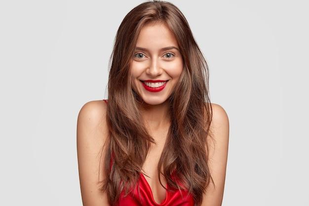 Pojęcie piękna, mody, makijażu i ludzi. urocza szczęśliwa kobieta z czerwoną szminką, pokazuje białe idealne zęby, ma zdrową skórę, długie ciemne włosy, odizolowana na białej ścianie, wyraża szczęście