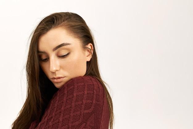 Pojęcie piękna, stylu i mody. strzał studio nieśmiałej pięknej młodej kobiety z idealną błyszczącą skórą, pozuje odizolowaną w ciepłym swetrze, jest zimna, ma nieśmiały wyraz twarzy, patrzy w dół
