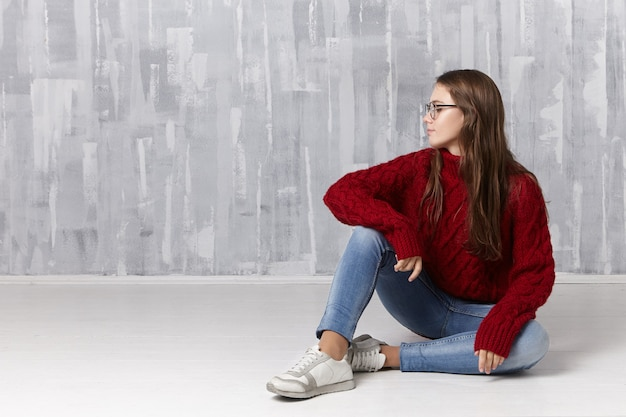 Pojęcie piękna, stylu, mody, młodzieży, ludzi i stylu życia. miła, urocza nastolatka z długimi luźnymi włosami siedzi na podłodze, w okularach, swetrze z golfem, dżinsach i trampkach