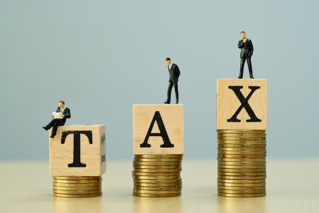 Pojęcie podatkowe. miniaturowy biznesmen i złote monety.